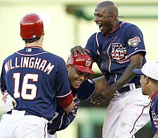Pudge is mobbed by teammates after his single in the ninth caps the Nats' game-winning three-run rally. (AP)