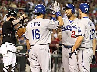 Matt Kemp (center) celebrates his second-inning homer -- an inning the Dodgers score six unearned runs. (AP)