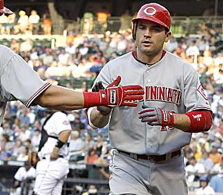 Joey Votto is greeted warmly after getting the Reds on the board with a home run in the first. (AP)