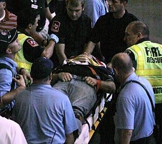 Paramedics attend to a fan who fell out of the second deck while trying to catch a foul ball.  (AP)
