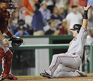 Buster Posey slides in safely at home to score the fourth run during the Giants' big seventh. (AP)