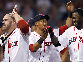 Kevin Youkilis (left) is the hero as he doubles in the tying run and also drives in the winner with a sac fly. (AP)