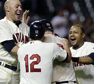 The Indians mob Austin Kearns after his game-winning RBI single in the bottom of the 11th inning.  (AP)