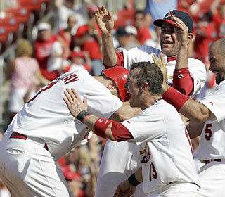 Matt Holliday takes a beating from his teammates after knocking in the game winner.  (AP)