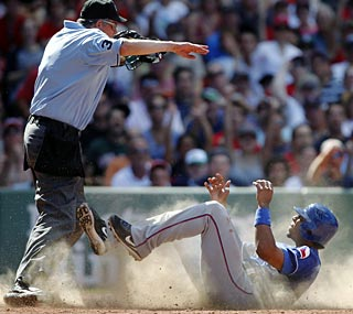 Elvis Andrus gets the safe call on a bang-bang play at home for the Rangers' final run.  (AP)