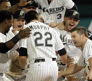 The Marlins wait for unlikely hero Donnie Murphy after he hits the winner in his fourth at-bat of the season.  (AP)