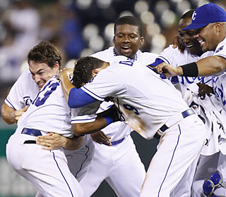 The Royals mob Alberto Callaspo (left) after he drives in the winning run with two outs in the 10th.  (AP)