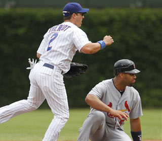 Ryan Theriot, left, looks to first after forcing out Albert Pujols during the first inning. (AP)