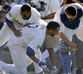 James Loney (bottom) receives a hearty greeting at home plate after his game-winning long ball.  (AP)