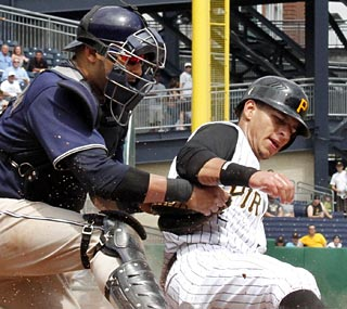 Ronny Cedeno beats Yorvit Torrealba's tag, but it's not enough to lift the Pirates to victory.  (AP)