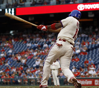 Jimmy Rollins and the Phils rally and score two runs following a lengthy rain delay. (AP)