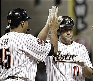 Lance Berkman is congratulated at home plate by teammate Carlos Lee after his 7th inning grand slam. (AP)