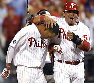 Wilson Valdez (left) is congratulated by Carlos Ruiz after producing the game-winning single in the 11th. (AP)