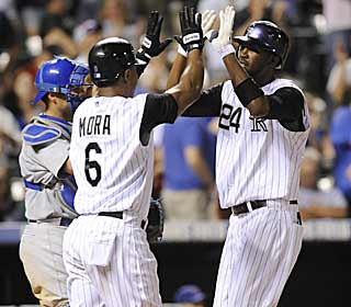 Dexter Fowler (right) hits a two-run jack in the eighth. It's one of the Rockies 13 hits that inning. (AP)