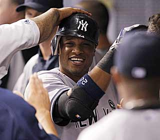Robinson Cano is warmly greeted in the dugout after his 21st home run gives New York the lead. (AP)