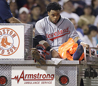 Indians rookie catcher Carlos Santana is taken off the field after sustaining a leg injury.  (AP)