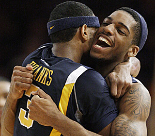 John Flowers hugs Devin Ebanks (3), who knocks down a career-high 20 points in the upset victory.  (AP)