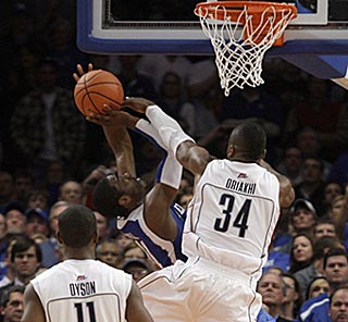 Alex Oriakhi fouls John Wall, who makes a tough shot for a three-point play that puts UK ahead 63-61.  (AP)