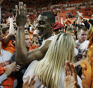 Obi Muonelo (17 points) and the Oklahoma State fans celebrate the upset of Kansas.  (AP)