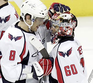 Alex Ovechkin and Jose Theodore celebrate after the Capitals notch a franchise-best 51st victory.  (AP)