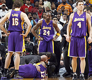The Lakers look on cautiously as their starting center Andrew Bynum is in obvious pain.  (Getty Images)