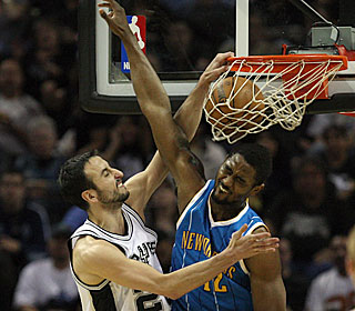 Manu Ginobili gets the best of Hilton Armstrong, dunking two of his 22 points.  (Getty Images)