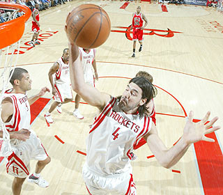 Look Mom, no eyes! Luis Scola gets up high and finishes with a career-high 18 rebounds. (Getty Images)