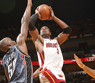 Dwyane Wade goes right at Emeka Okafor to help the Heat shoot a season-high 56 percent.  (Getty Images)