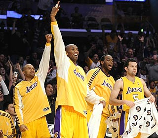 Kobe Bryant and Co. watch as the second unit finish up the Lakers' 50th victory of the season.  (AP)