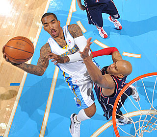 J.R. Smith attacks the basket and goes at Vince Carter during Denver's third straight win.  (Getty Images)
