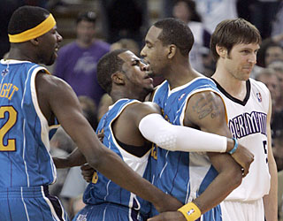 The Hornets swarm Rasual Butler (second from right), who ends the game with a buzzer-beating 3.  (AP)