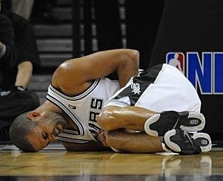 Tony Parker doubles over in pain after a hard fall, ending his 17-point night early.  (US Presswire)