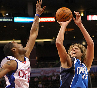 Marcus Camby can't block Dirk Nowitzki, who makes 9 of 19 shots to finish with 24 points. (Getty Images)