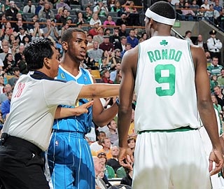 A referee makes sure nothing gets out of hand between Chris Paul and Rajon Rondo.  (Getty Images)