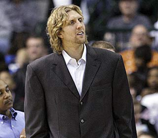 Dirk Nowitzki has a front-row seat for the Mavs win after injuring his elbow Friday night. (AP)
