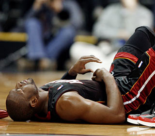 Although D-Wade returns from a hard collision, he can't save the road-weary Heat from losing ugly.  (AP)