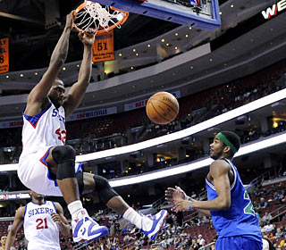 Elton Brand, who finishes with 21 points, gives the Wolves' Corey Brewer a free lesson in dunking.  (AP)