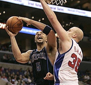 Carlos Boozer (left) outperforms All-Star Chris Kaman, and Utah improves to 13-1 since Jan. 8.  (AP)