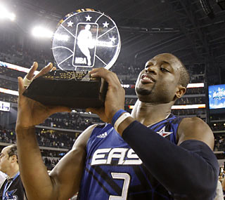 Dwyane Wade hoists up his MVP trophy after lifting the East with his 28-point, six-rebound, 11-assist performance.