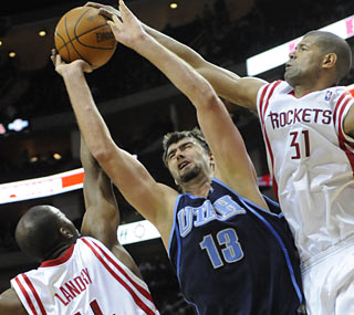 The Rockets offer little room for Mehmet Okur to work, but the Jazz center still finishes with 21 points.  (AP)