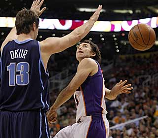 Steve Nash shows some flash with a behind-the-back pass around Mehmet Okur. (AP)