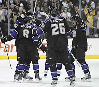 Drew Doughty (8) gets mobbed by his teammates after scoring the game winner.  (AP)