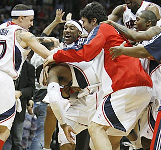 The Atlanta Hawks are understandably excited after witnessing Josh Smith's walk-off put-back dunk.  (AP)