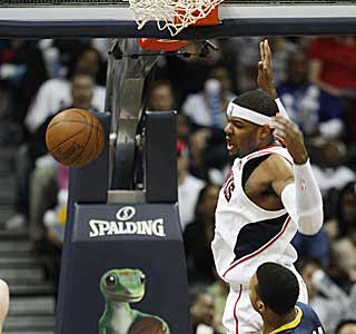 The Hawks' Josh Smith emphatically throws down a dunk over Brandon Rush of the Pacers. (AP)