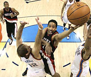 The Blazers' Marcus Camby (rear) looks surprised by Andre Miller's ability to convert the layup. (AP)