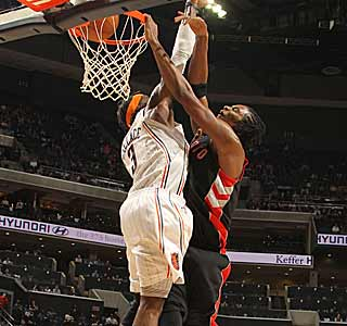The Raptors' Chris Bosh posterizes Gerald Wallace on his way to scoring 22 points. (Getty Images)