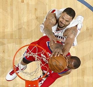 Charlotte's Tyson Chandler (top) battles Philadelphia's Marreese Speights under the basket.  (Getty Images)