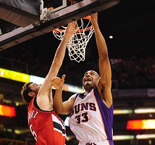 Grant Hill (right) beats Rudy Fernandez to the rim en route to a 10-of-11 shooting performance.  (AP)