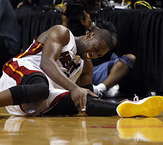 Dwyane Wade hurts his left leg late and can only watch his team fall behind the Celtics 3-0.  (AP)
