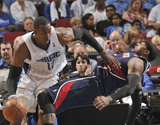 Dwight Howard (21 points, 12 boards) helps the Magic push aside Josh Smith and the Hawks.  (Getty Images)